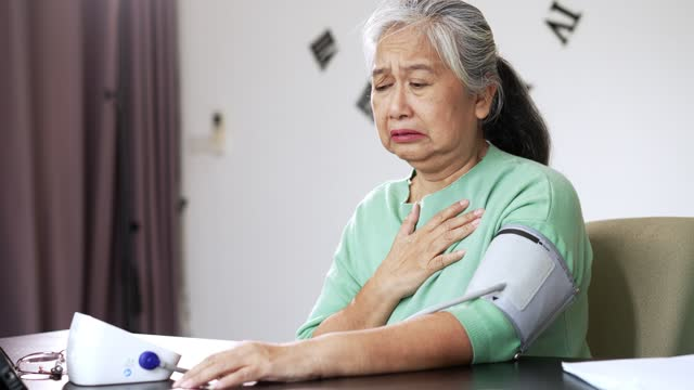 Senior woman measuring blood pressure by herself at home