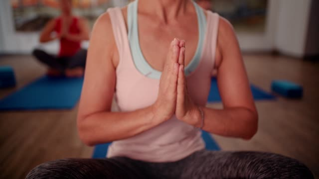 Senior woman mediating in yoga class in the lotus position video