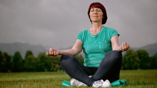 SLO MO DS Senior woman meditating in the park video