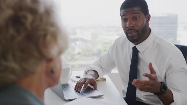 senior woman meeting with male financial advisor in office - professione finanziaria video stock e b–roll