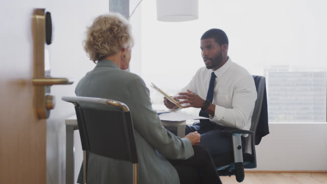 senior woman meeting with male financial advisor in office - scambio d'idee video stock e b–roll