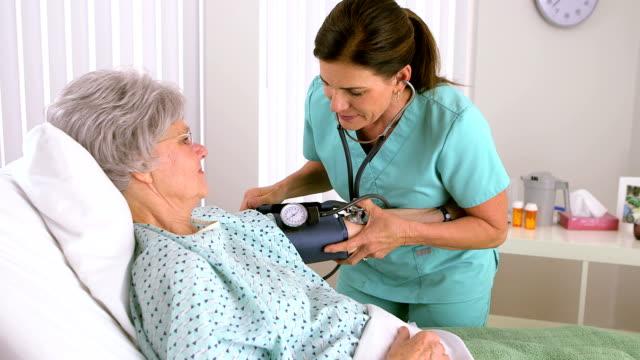 Senior woman nurse checking patient's blood pressure Senior woman nurse checking patient's blood pressure blood pressure gauge stock videos & royalty-free footage