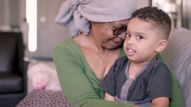 vídeos de stock, filmes e b-roll de uma mulher sênior da descida africana com cancro está em casa que prende seu neto. ela parece estar contente e em paz. - consciência negra