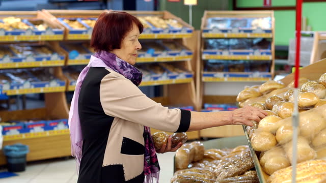 A senior woman of age buys bread at the grocery store. Slow motion.