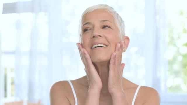 vídeos de stock, filmes e b-roll de mulher sênior oman que toca em sua pele. - skincare