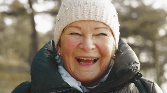 senior woman on a hike looking into camera - woman portrait forest video stock e b–roll