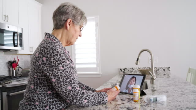 senior woman on a virtual doctor visit - social distancing stock videos & royalty-free footage