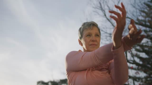 senior woman outdoor yoga fitness - rozciągać filmów i materiałów b-roll