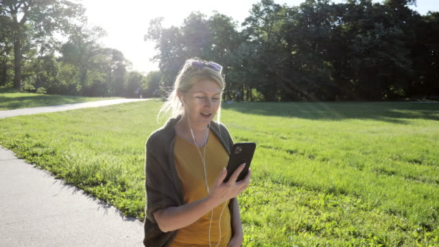 senior kvinna utomhus på vårdagen i parken med hjälp av telefon för videosamtal - slow motion video - naturparksområde bildbanksvideor och videomaterial från bakom kulisserna