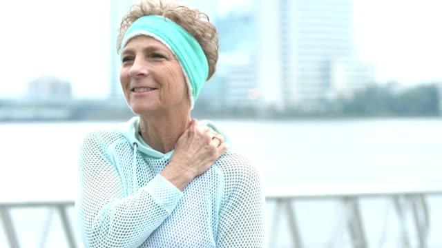kadın kıdemli açık havada, ağrılı omuz, gülümsüyor losyonları - hayvan eklemi stok videoları ve detay görüntü çekimi
