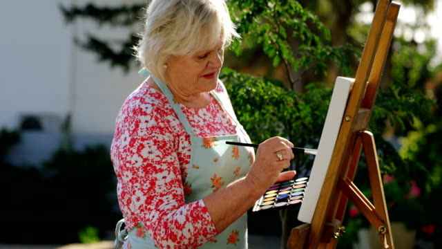 senior woman painting on canvas in the garden 4k - 60 69 anni video stock e b–roll