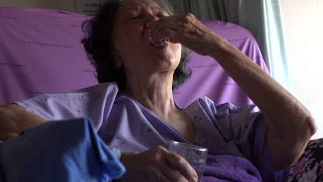 Senior woman patient taking medicines in hospital video