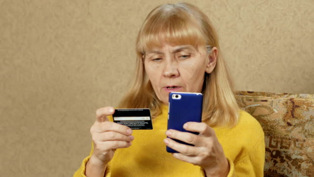 senior woman pay for purchases in the internet bank credit card. she carefully introduces a credit card number to the phone. home shopping concept - fraud stock videos & royalty-free footage