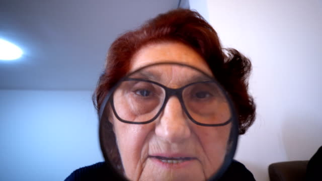 Senior woman peering through a magnifying glass video