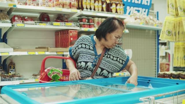 senior woman pick up products from refrigerator - замороженные продукты стоковые видео и кадры b-roll