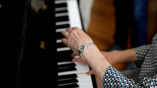 Senior woman playing piano for guest