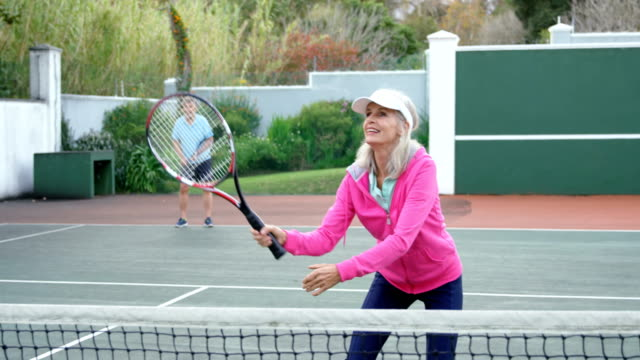stockvideo's en b-roll-footage met senior vrouw tennissen in tennisbaan 4k - sportiviteit