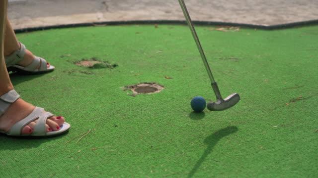 シニアの女性はミニゴルフをし、穴に青いボールを入れる前に簡単なショットを逃します。緑のカーペットの上に彼女の足の詳細 - 不吉点の映像素材/bロール