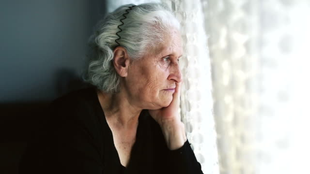 dolly: senior woman porträt blick durch fenster hinter dem vorhang - blick durchs fenster stock-videos und b-roll-filmmaterial