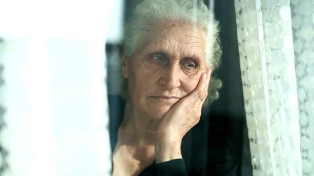 Senior woman portrait looking through window behind the curtain Senior woman portrait looking out the window behind the curtain middle east stock videos & royalty-free footage