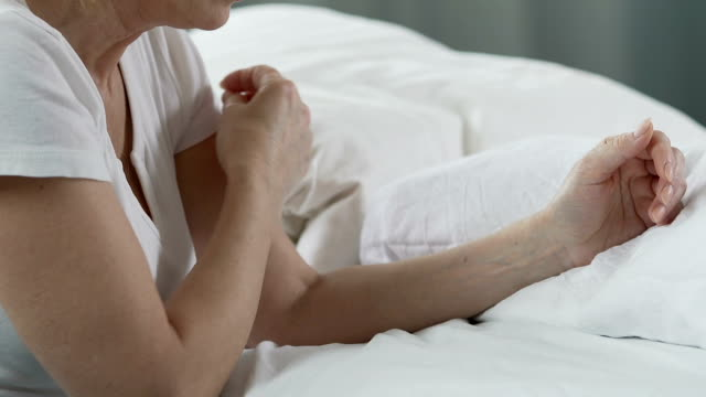 Senior woman praying at her bed and crossing herself, Catholic Christian values video