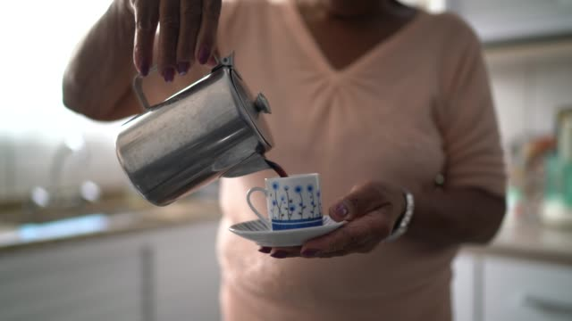 Senior woman prepares coffee in morning at home
