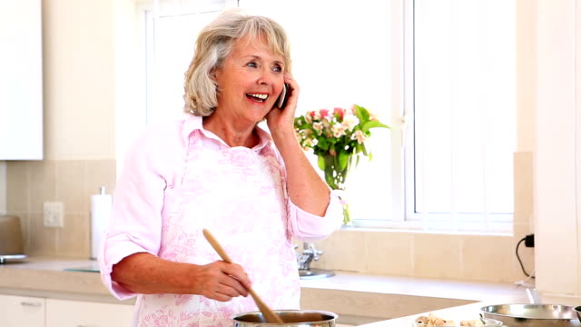 Senior woman preparing a meal and answering phone video
