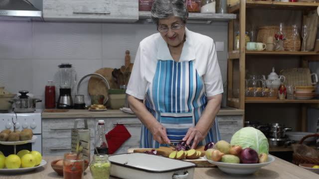 Senior woman preparing food Senior woman preparing food in domestic kitchen grandmother stock videos & royalty-free footage