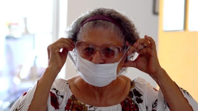 yüzüne koruyucu maske koyan yaşlı kadın - maske stok videoları ve detay görüntü çekimi