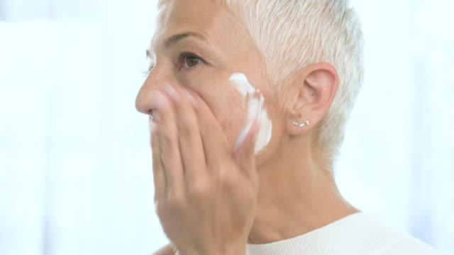 クリームを入れるシニア女性。 - 人の肌点の映像素材/bロール