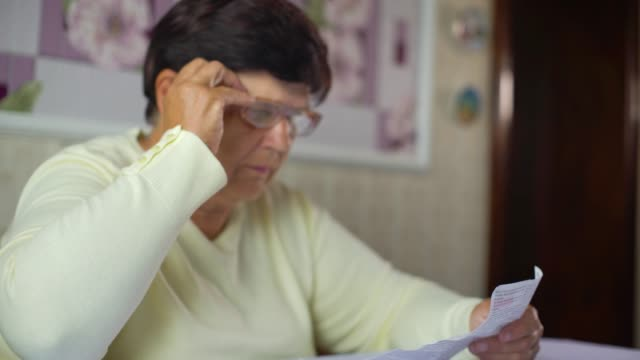 Senior woman putting eyeglasses on and reading information sheet of prescribed medicine at home