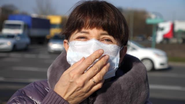 senior in der frau, die eine gesichtsmaske anzieht. sicherheit an öffentlichen orten während coronavirus - krankheitsverhinderung stock-videos und b-roll-filmmaterial
