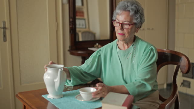 Senior woman reading a book during afternoon tea at home. video