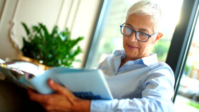 senior woman reading a magazine. - krótkie włosy filmów i materiałów b-roll