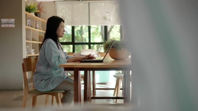 stockvideo's en b-roll-footage met senior vrouw lezen boek - woman home magazine