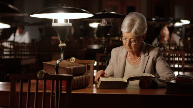 DS Senior woman reading in library at night video
