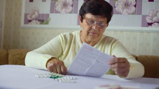 vídeos y material grabado en eventos de stock de senior mujer leyendo la hoja de información de medicinas recetadas, sentado en la mesa en casa - receta instrucciones
