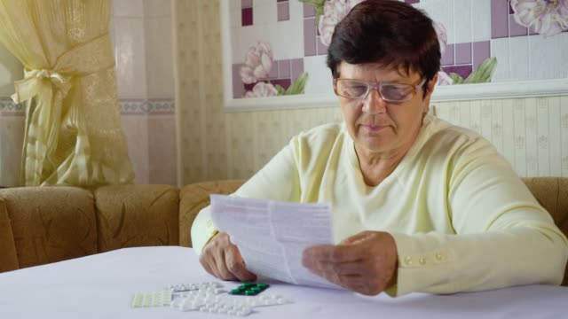 Senior woman reading information sheet of prescribed medicine sitting at table at home