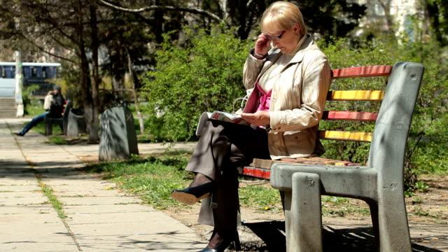 Senior Woman Reading Magazine In The Park video