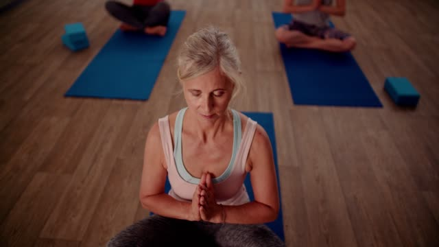 Senior woman relaxing during focused breathing exercise in yoga class video