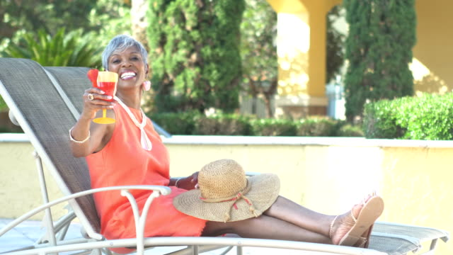 Senior woman relaxing on lounge chair, tropical drink A senior African-American woman in her 70s relaxing on a lounge chair on a pool deck, holding a tropical drink cocktail, smiling at the camera. lounge chair stock videos & royalty-free footage