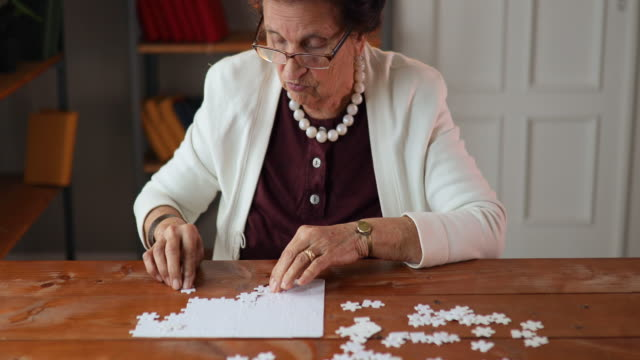 senior woman relaxing with jigsaw puzzle at home - puzzle video stock e b–roll