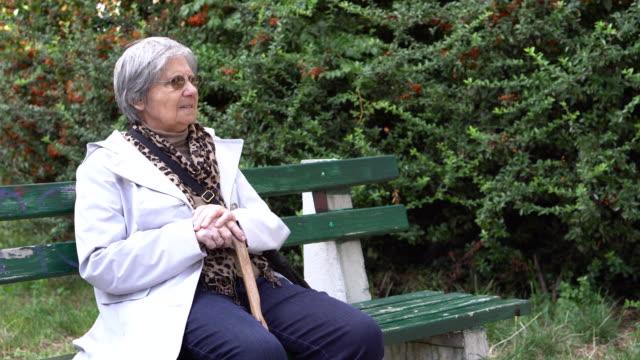 高齢者の女性の出るご休息 - ベンチ点の映像素材/bロール
