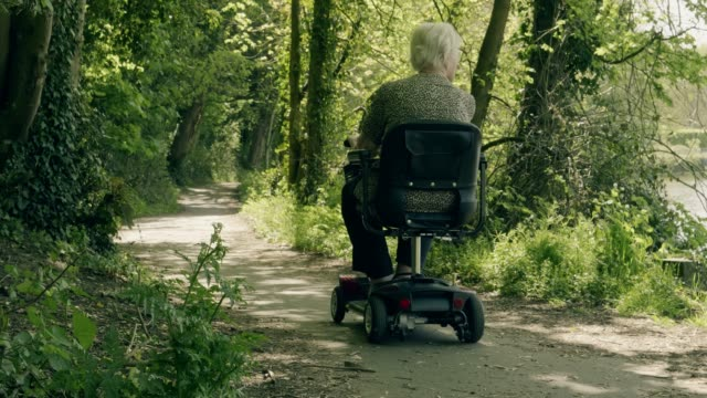 Senior woman riding a mobility scooter. Rear view. A senior woman riding a mobility scooter away from camera through a riverside woodland area, rear view. This is a 10 second clip, also available as 'part of a series' is a longer 25 second version. wheelchair stock videos & royalty-free footage