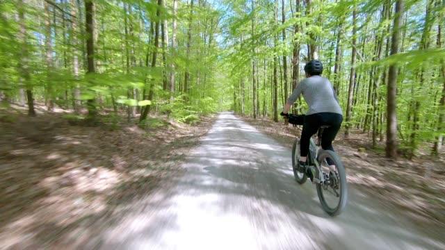 senior woman riding electric mountain bike in spring forest - percorso per bicicletta video stock e b–roll