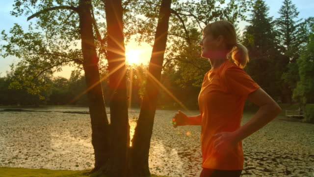 SLO MO TS Senior woman running along lake at sunset video