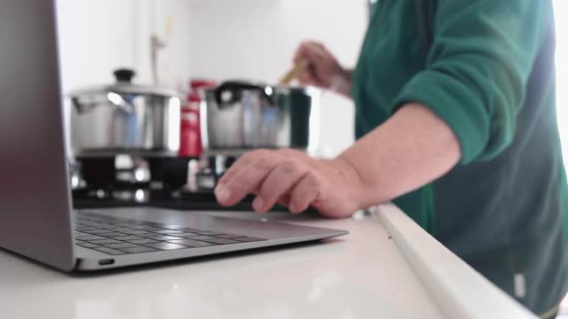 vídeos de stock e filmes b-roll de senior woman searching for new recipes with laptop on kitchen counter - eternidade