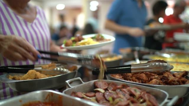 Senior woman selecting food on self service