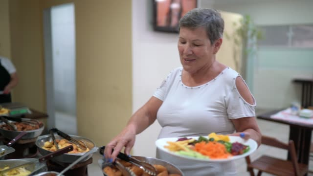 senior woman selecting food on self service - фуршет стоковые видео и кадры b-roll
