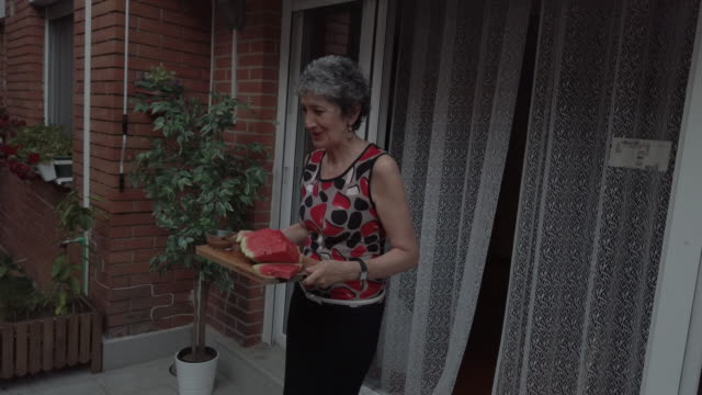 Senior Woman Serving Watermelon Slices To Her Friends
